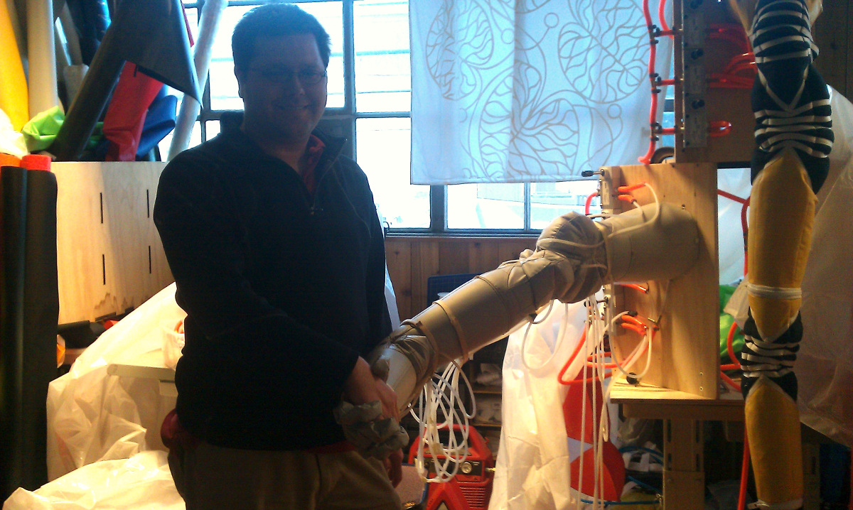 Travis Deyle shaking hands with an inflatable robot at Otherlab